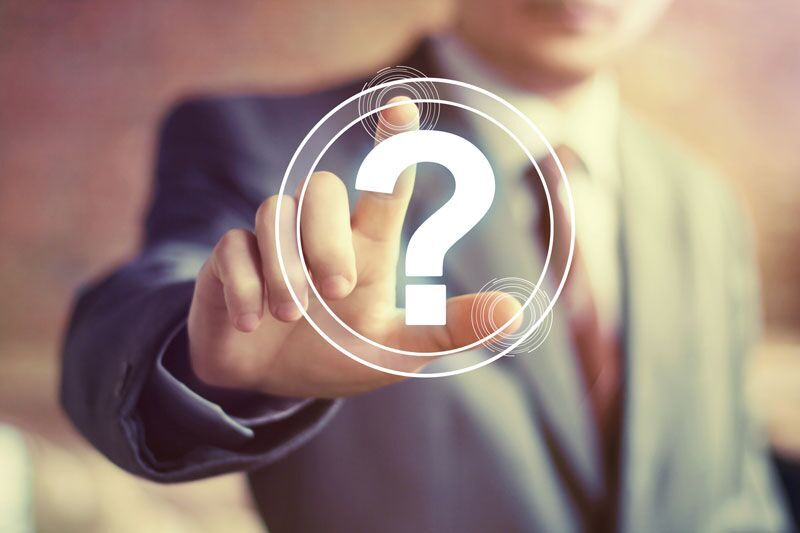 man in suit pressing question mark icon, workers comp FAQs