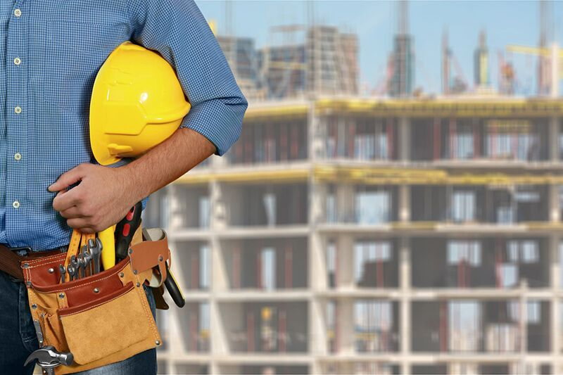 worker carrying hardhat, preventing stuck-bu-object injuries