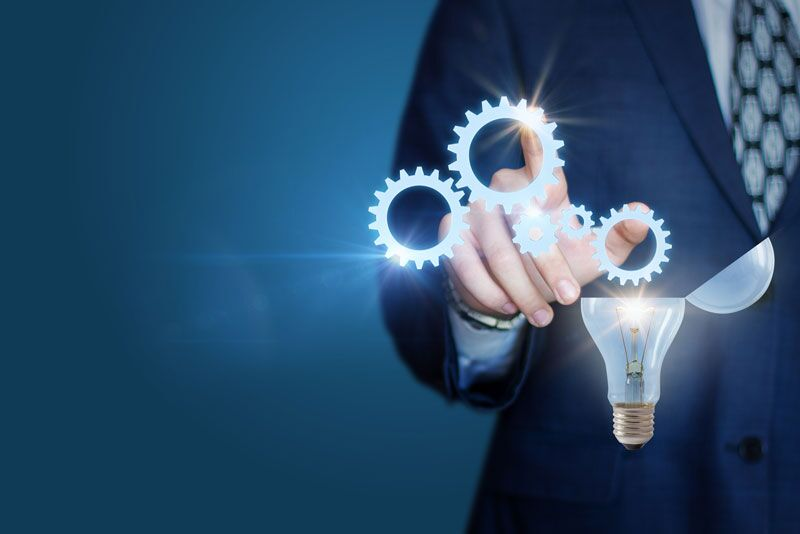 businessman hitting virtual pic of cogs and light bulb, using tech to address workplace risk