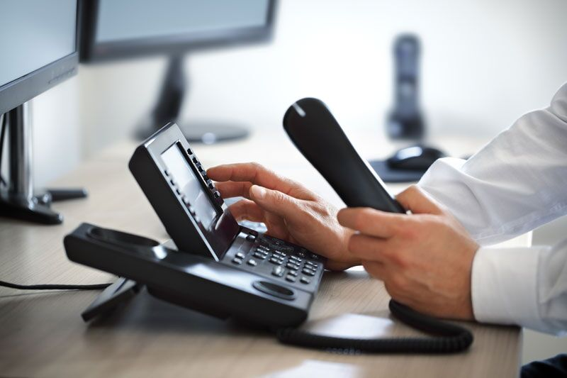 business owner calling insurance company, avoid these workers comp reporting mistakes