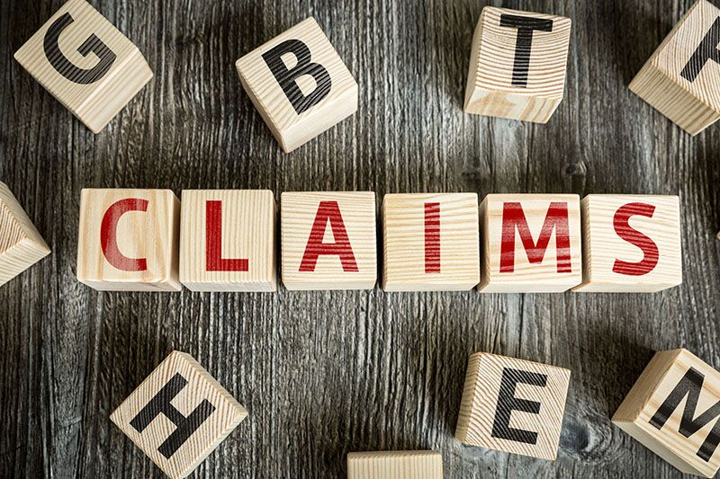 "wood blocks spelling out ""claims,"" disputing sake workers comp claims"