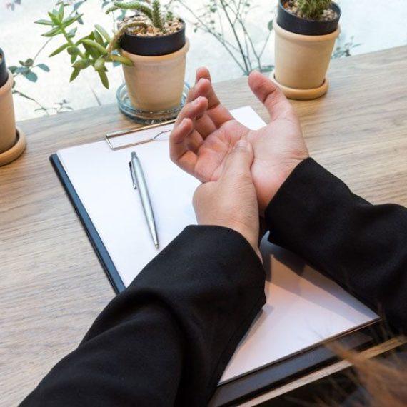 worker rubbing sore wrist, preventing office-staff injuries