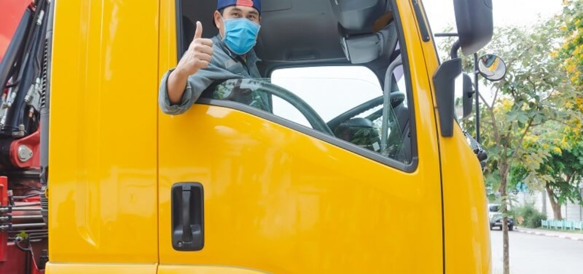 Truck driver wearing mask in truck